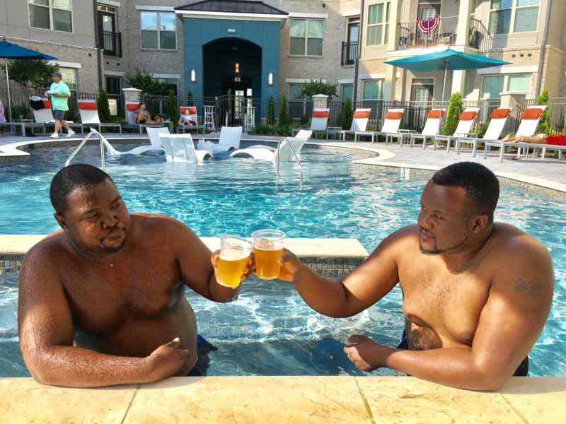 2 guys in pool doing a cheers