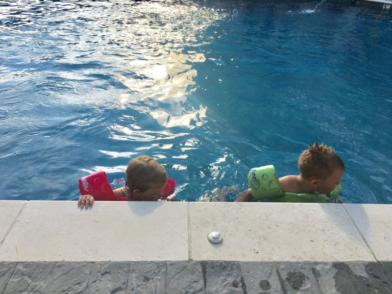 2 kids in pool with swimmies
