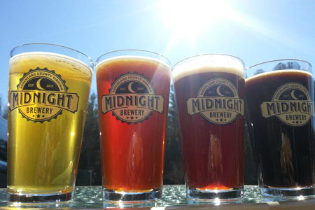 4 different types of Midnight beers in pint glasses