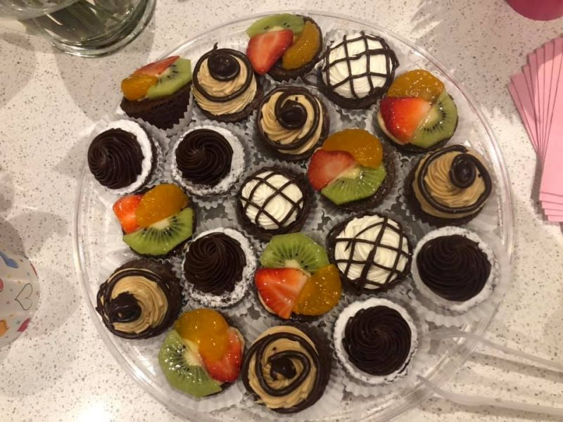 Various cupcakes with fruit toppings