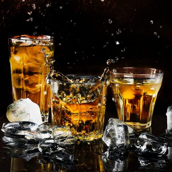 Glasses of bourbon with ice next to them