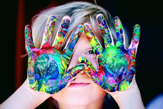 Kid holding up hands with colorful paint